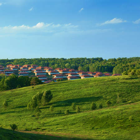 Green meadow against blue sky and small town photo