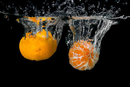 Fresh tangerines dropped into water with bubbles on black photo