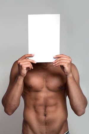 homme nu: Musculaire homme nu tenant du papier blanc vide