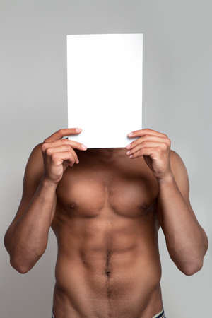 Muscular naked man holding white empty paper photo