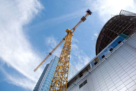 tower crane: Modern building under construction against blue sky Stock Photo