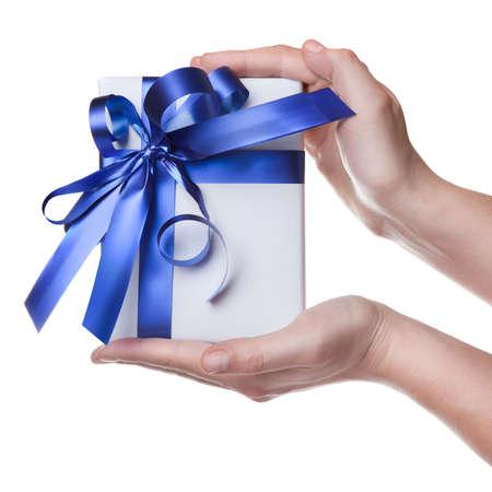 dar un regalo: Manos sosteniendo el regalo en paquete con cinta azul, aislado en blanco