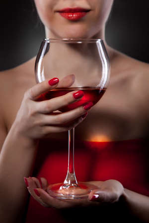 woman in red holding wine glass and smiles Stock Photo