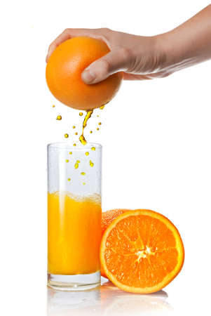 squeezing orange juice pouring into glass isolated on white photo