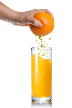 verre de jus: serrant le jus d'orange verser dans le verre isol� sur blanc Banque d'images