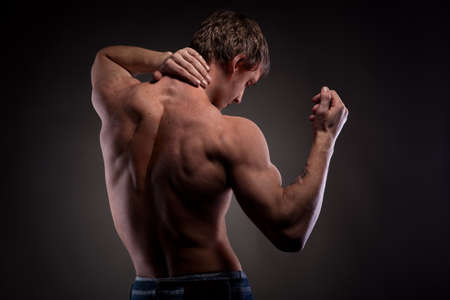naked man: Muscular naked man from back on black Stock Photo