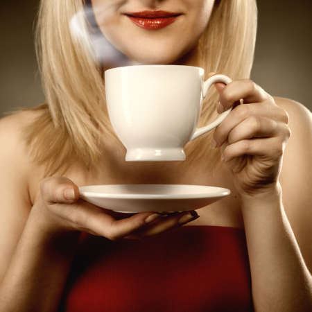 woman in red holding cup and smiles photo