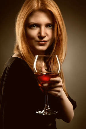woman with red hair holding wine glass photo