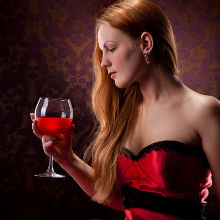 elegant woman with red hair holding wine glass Stock Photo