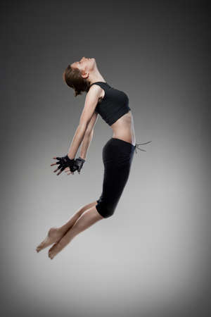 jumping young dancer on black Stock Photo - 8851400