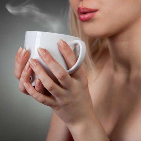 woman holding hot cup and blowing on it Stock Photo - 8996567