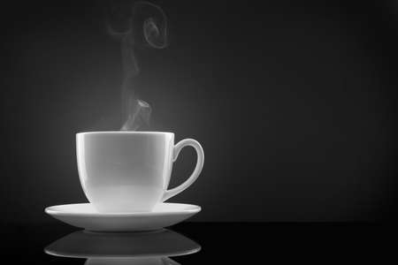 hot coffee: white cup with hot liquid and steam on black