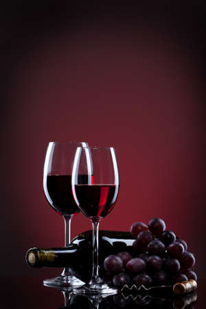 Wine in glasses with grape and bottle on red photo