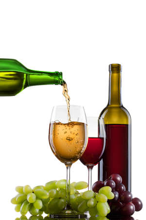 filling bottles: White wine pouring into glass with grape and bottles isolated