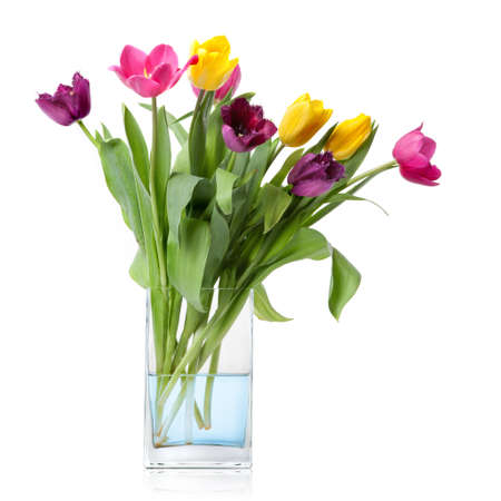 april flowers: bouquet from tulips in glass vase isolated on white Stock Photo