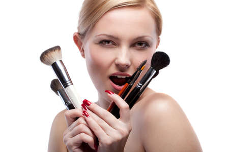 Young smiling woman with make up brushes isolated on white Stock Photo - 9535281