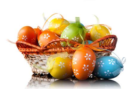 pascuas navide�as: huevos de Pascua de color en la cesta aislados en blanco Foto de archivo
