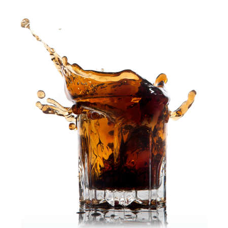 still: splash of cola in glass isolated on white