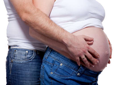 Man and womans hands over pregnant belly on white photo