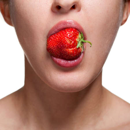 hot lips: Young woman biting strawberry isolated on white