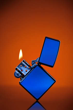 Blue zippo lighter with flame on orange background photo