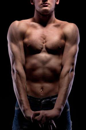 Muscular naked man on black photo