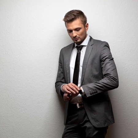 black tie: apuesto hombre de negocios mira su reloj en blanco Foto de archivo