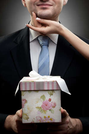 birthday suit: closeup portrait of businessman holding gift with woman hand Stock Photo