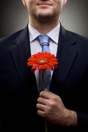 birthday suit: closeup portrait of smiling businessman holding red flower