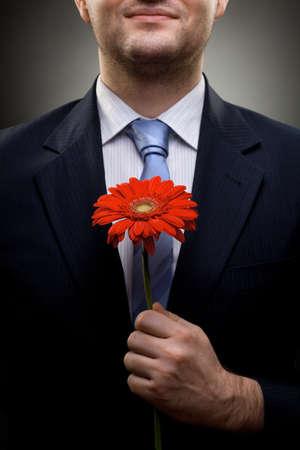 flores de cumplea�os: Retrato de hombre de negocios sonriente sosteniendo flores rojas Foto de archivo