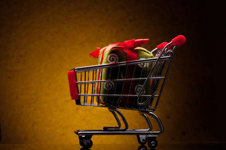 shopping cart with gift on yellow background photo