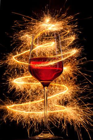 El vino en cristal con luces de bengala quema sobre fondo negro