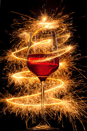 Wine in glass with burning sparklers on black background