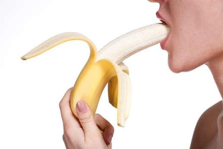 comiendo platano: La mujer joven morder plátano aislado en blanco Foto de archivo
