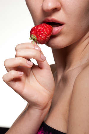Young woman biting strawberry isolated on white photo
