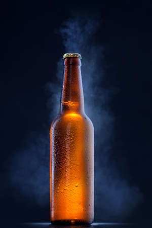 dew cap: Cold beer bottle with drops, frost and vapour on black Stock Photo