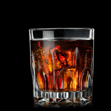 cola with cognac in glass on black photo