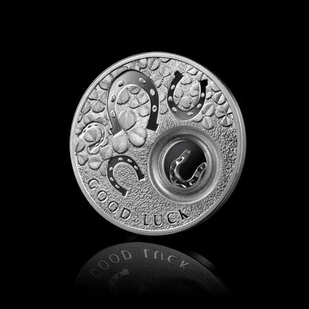 silver coin with horseshoes isolated on black photo