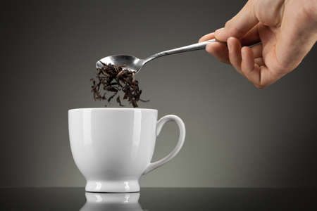 strew: tea pour out into white cup on grey