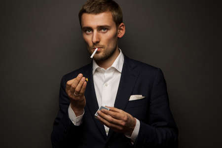 portrait of handsome businessman with cigarette on black photo