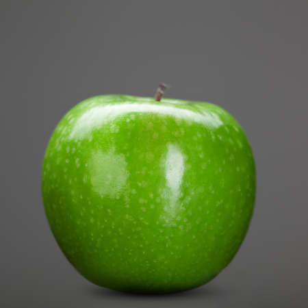 green apple isolated on grey photo
