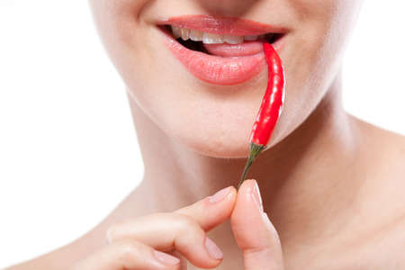 female tongue: Young woman with chili pepper isolated on white