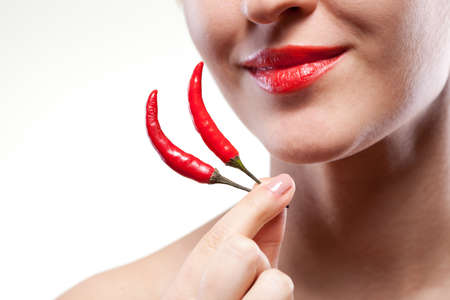 Young woman with chili pepper isolated on white Stock Photo - 13028071