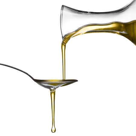 Verser l'huile sur la cuillère isolé sur blanc Banque d'images