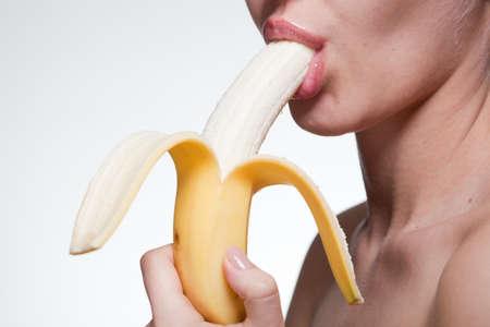 licking in isolated: Giovane donna mordere banane isolato su bianco
