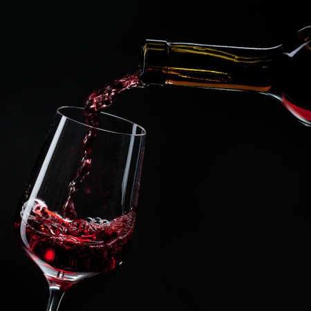 red wine pouring into wine glass isolated on black photo
