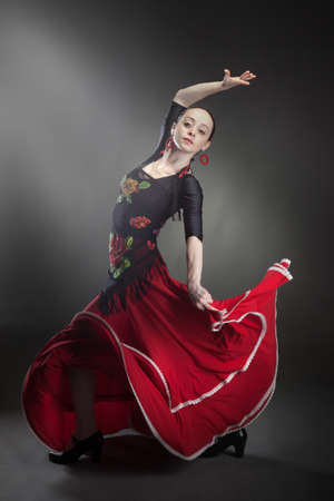 young woman dancing flamenco on black photo