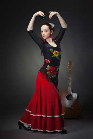 young woman dancing flamenco with castanets on black photo