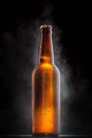 amber light: Cold beer bottle with drops, frost and vapour on black Stock Photo