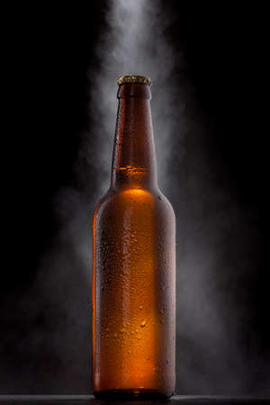 vapour: Cold beer bottle with drops, frost and vapour on black Stock Photo